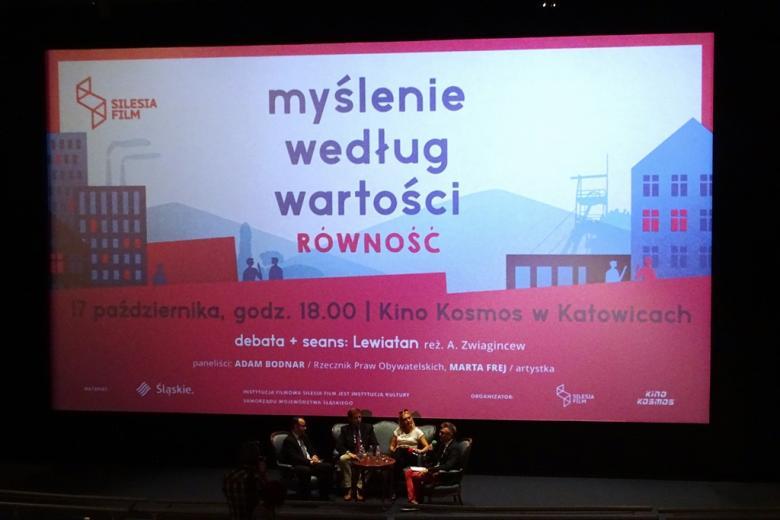 Trzej mężczyźni i kobieta rozmawiają w panelu. Za nimi ogromny napis na biało0czerwonym tle: Myślenie według wartości. Równość