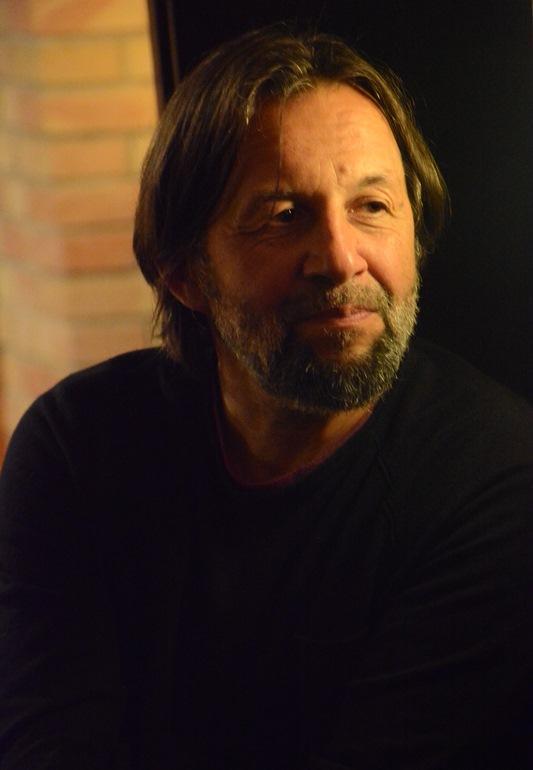 Mężczyzna z brodą i w ciemnym swetrze