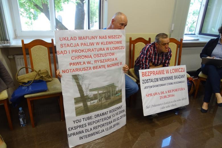 Ludzie trzymają plakaty z opisem krzywdy, jaka ich zdaniem spotkała ich w sądzie