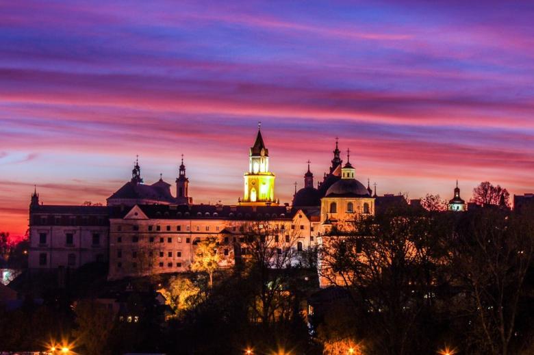 Wielobarwna fotografia zamku w Lublinie nad miastem o zachodzie słońca