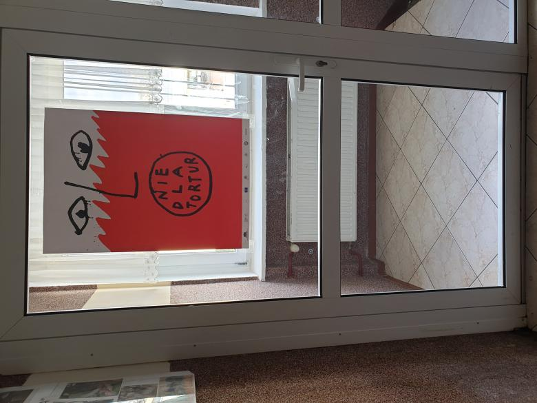 Na zdjęciu widać przeszklone drzwi, na których naklejono plakat przedstawiający biało-czerwoną twarz z napisem: nie dla tortur