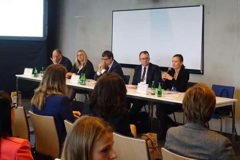 Zdjęcie: panel, trzech mężczyzn i dwie kobiety przy stole, kobieta mówi