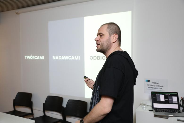 Męzczyzna przed slajdami z napisami: twórcami, nadawcami, odbiorcami