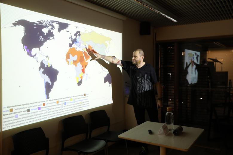 Mężczyzna przed slajdem z mapą świata