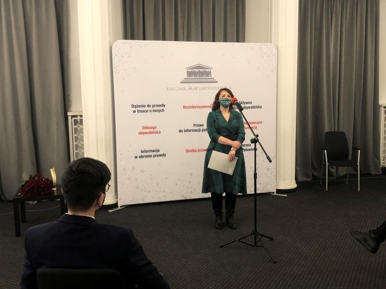 Kobieta w zielonej sukni przed mikrofonem