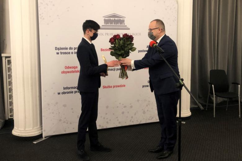Mężczyzna wręcza młodemu człowiekowi bukiet czerwonych róż