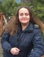 Kobieta w ciemnej kurtce w plenerze