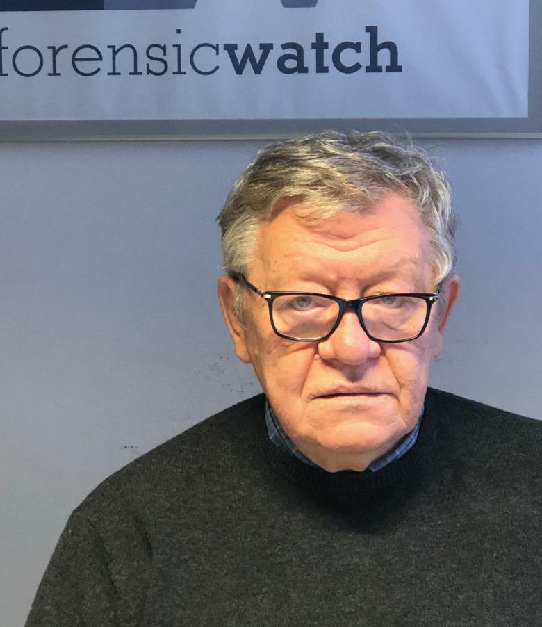 """Mężczyzna w ciemny swetrze na tle angielskiego napisu """"ForensicWatch"""""""