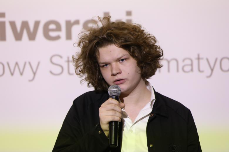 Młody mężczyzna mówi do mikrofonu