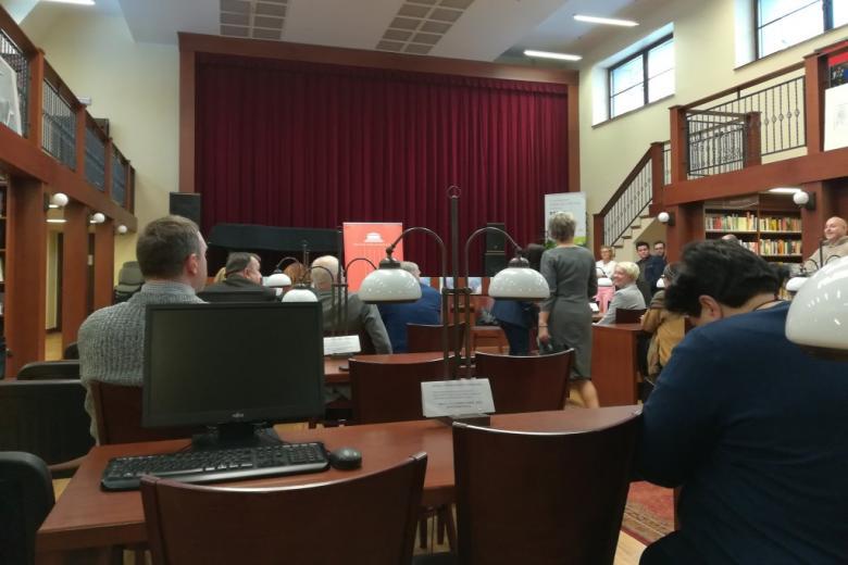 Sala biblioteczna. Ludzie zajmują miejsca przy stołach