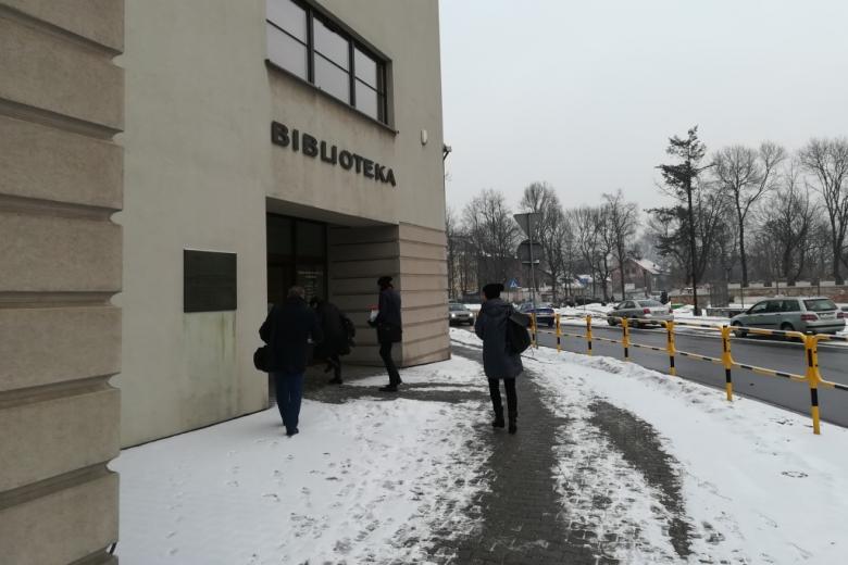 Ludzie wchodzą do budynku z napisem Biblioteka