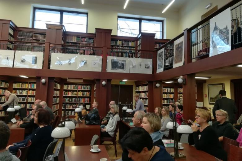 Widok na salę biblioteczną i antresole, na której siedzą ludzie młodzi