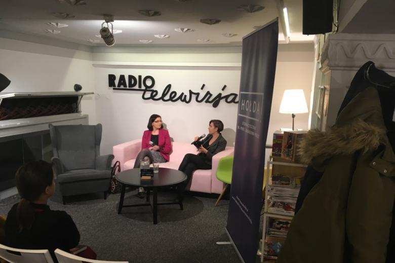 Dwie kobiety rozmawiają na kanapie, na ścianie napis Radio i Telewizja
