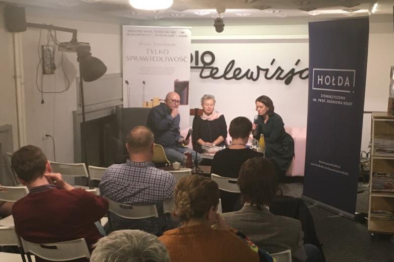 Trzy osoby rozmawiają na kanapie, na ścianie napis Radio i Telewizja
