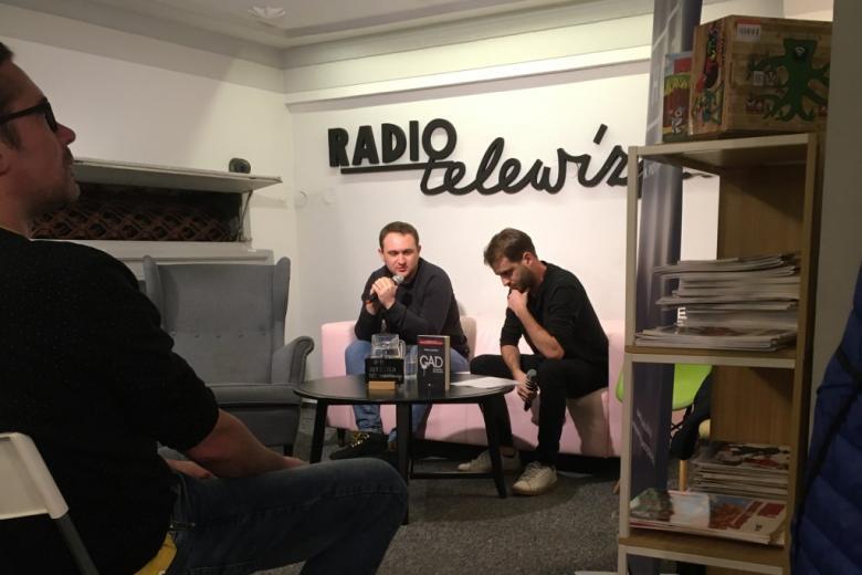 Dwaj mężczyźni rozmawiają na kanapie, na ścianie napis Radio i Telewizja
