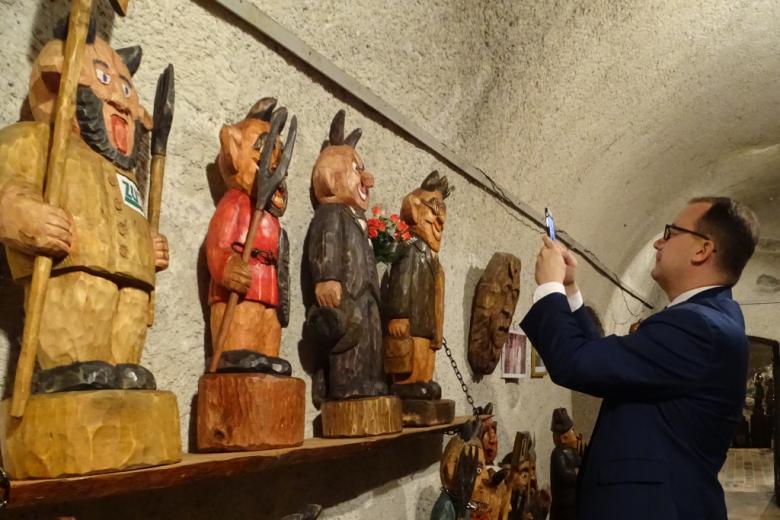 Mężczyzna fotografuje drewniane diabły stojące na półce