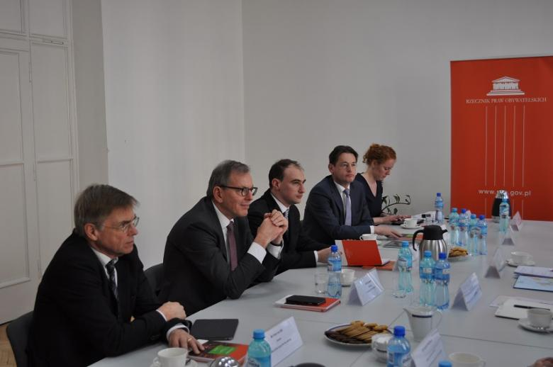 zdjęcie: kilka osób siedzi po jednej stronie białego stołu