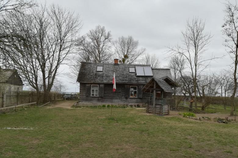 Drewinany domek i białoczerowna flaga