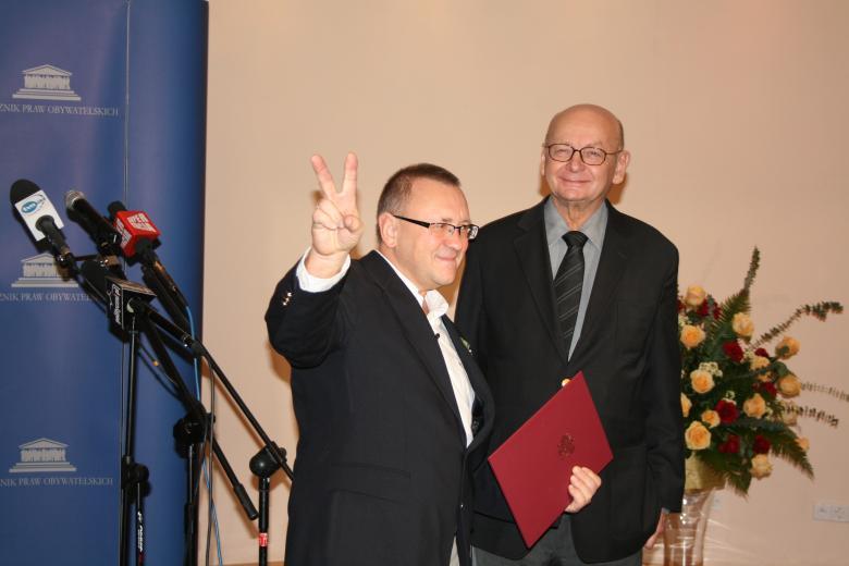 Dwaj mężczyźni, jeden podnosi rękę w znaku V