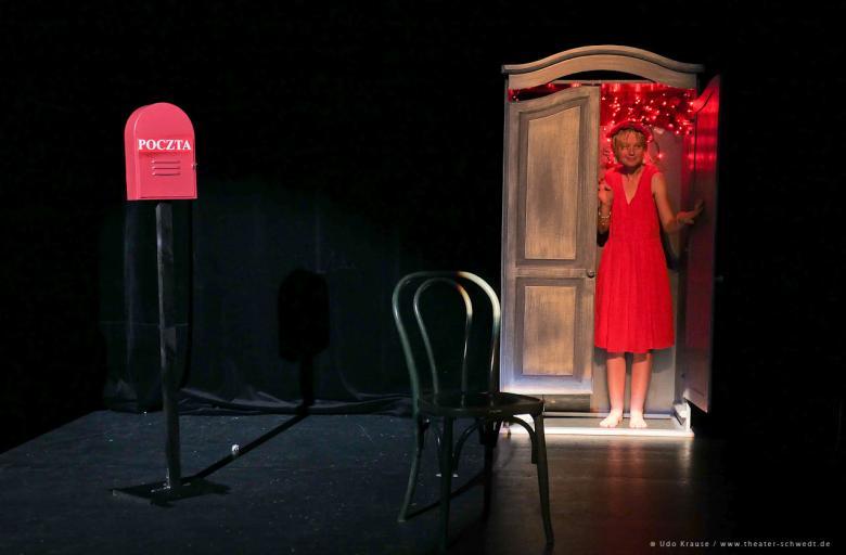 Aktorka teatru Bomba Bomba w czerwonej sukience stoi w szafie