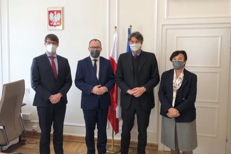 Trzech mężczyzn i kobieta pozują do zdjęcia na tle polskiej i unijnej flagi
