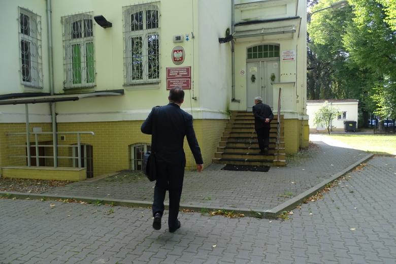 Mężczyzna wchodzi do zaytkowego budynku, w którym znajduje się poradnia