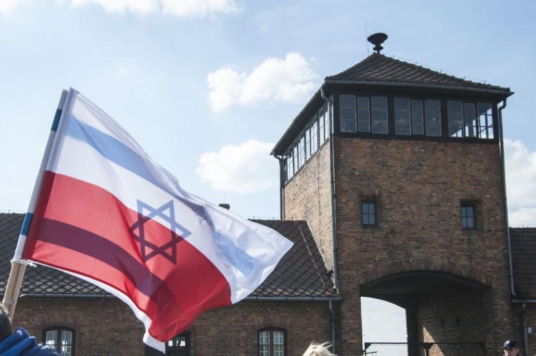 flaga polska i izraelska na tle byłego niemieckiego obozu zagłady