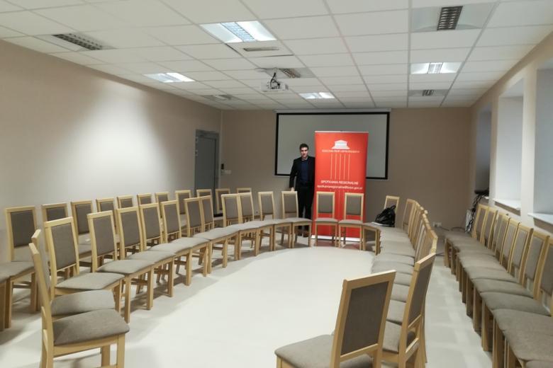 Pusta sala z krzesłami ustawionymi w kręgu, banner RPO, młody męzczyzna