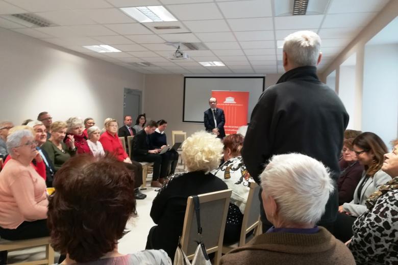Ludzie siedzą na spotkaniu, mężczyzna stojąc opowiada o swoich sprawach