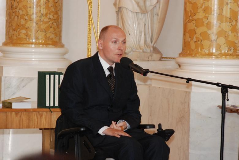 Mężczyzna na wózku mówi do mikrofonu na sali ze złoceniami