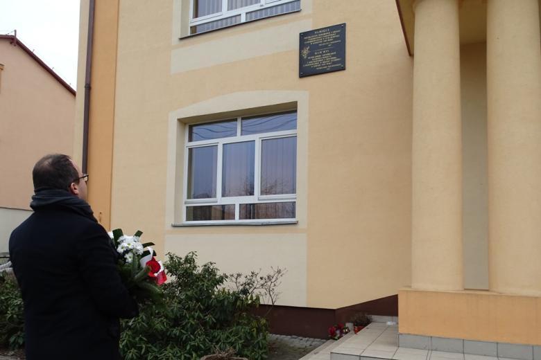 Budynek szkoły, na ścianie wisi tablica, męzczyzna stoi przed nią z bukietem biało-czerwonych kwiatów
