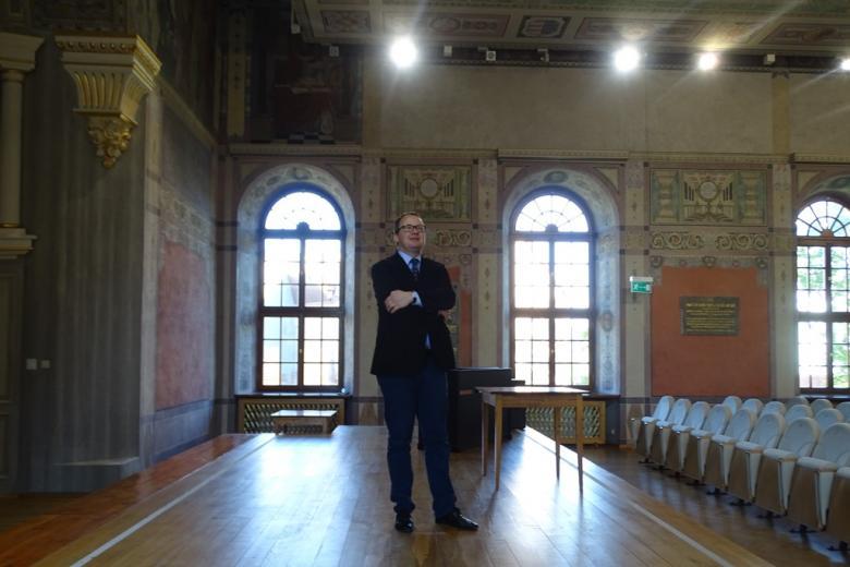 Mężczyzna w zabytkowej wielkiej sali z freskami