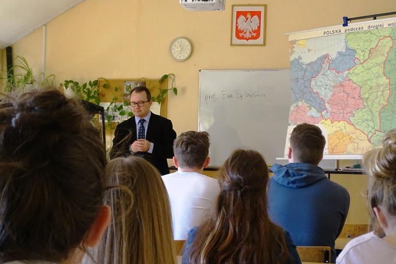 """Lekcja. Męzczyzna przy tablicy. Na niej napisane """"Ewa Łętowska"""""""