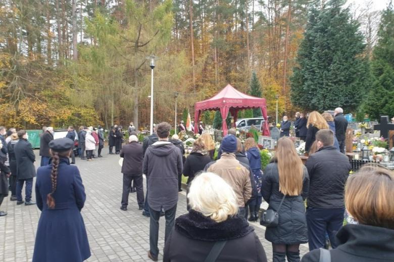 Osoby uczestniczą w pogrzebie na cmentarzu