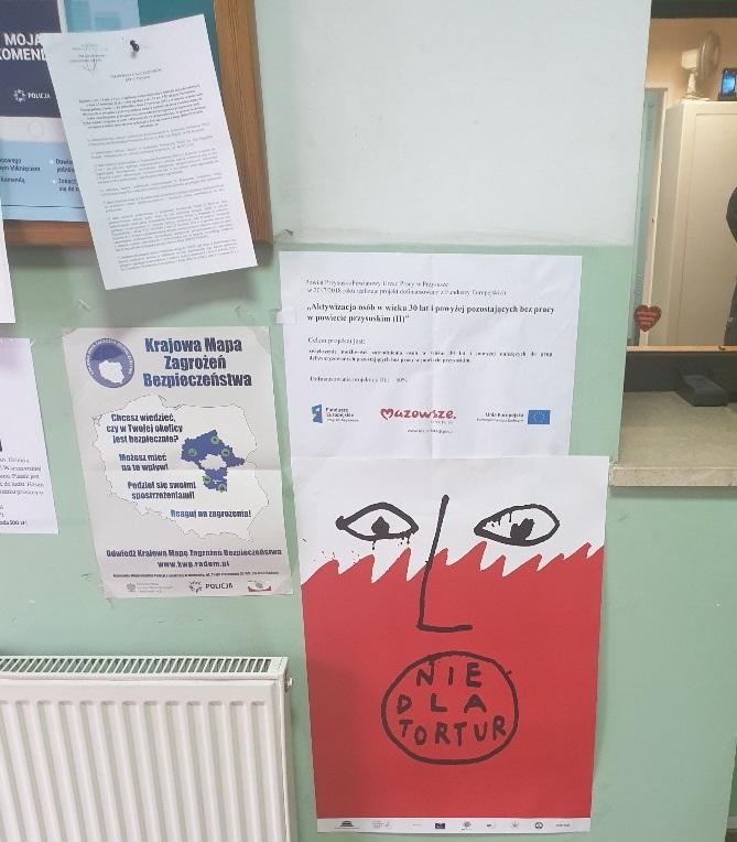 Na zdjęciu widać zieloną ścianę z naklejonymi kartkami, na wprost wisi plakat przedstawiający biało-czerwoną twarz z napisem: nie dla tortur