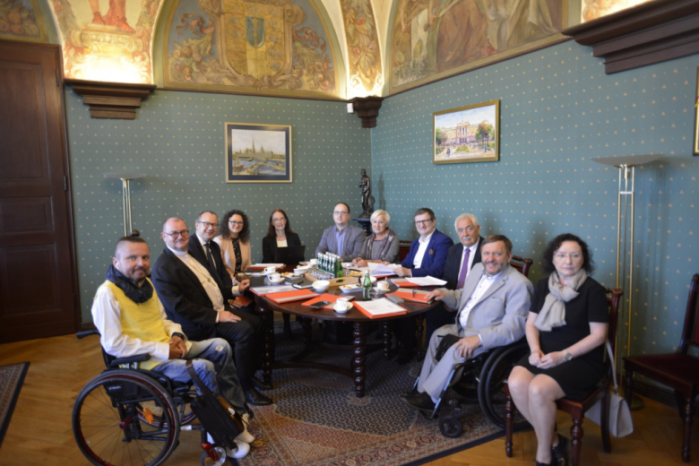 Ludzie przy stole, po lewej kolorowo ubrany mężczyzna na wózku