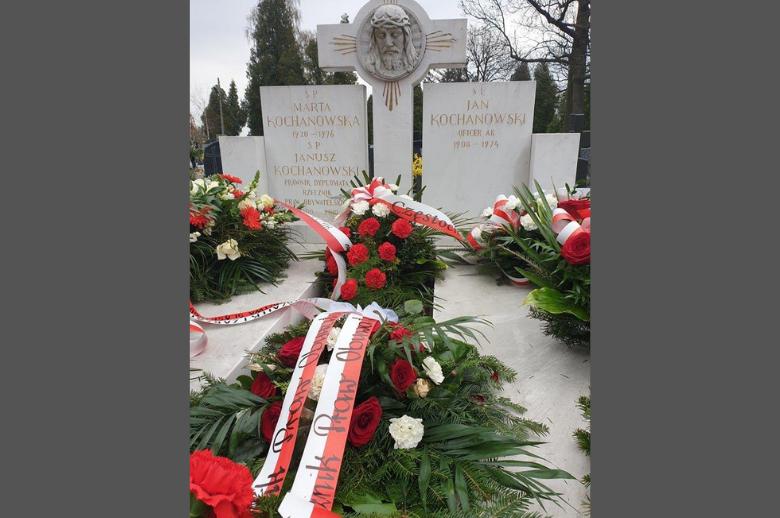 grób z biało-czerwonymi wiązankami kwiatów