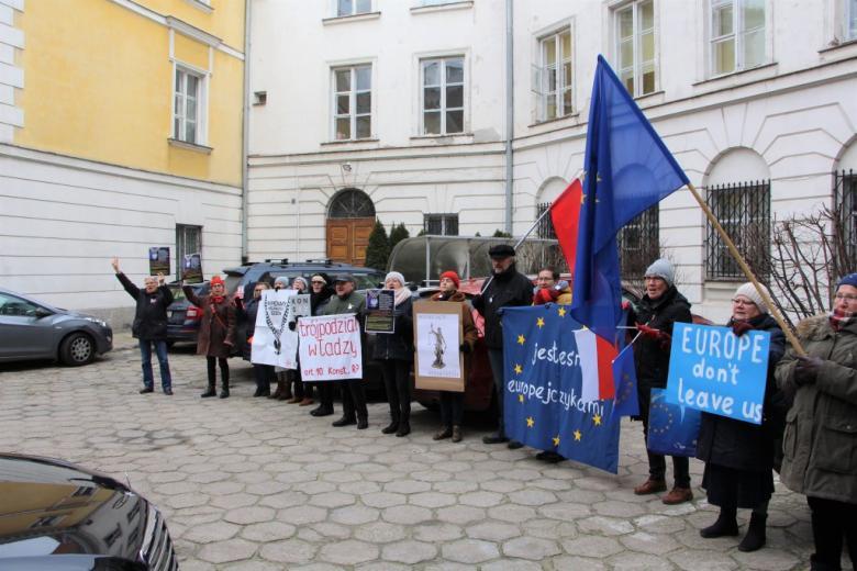 Osoby stoją, trzymając flagi i transparenty