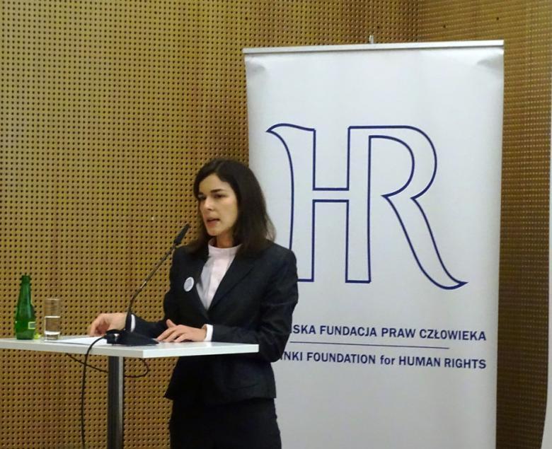 Zdjęcie: młoda kobieta stoi przy mównicy, za nią banner z logiem HR