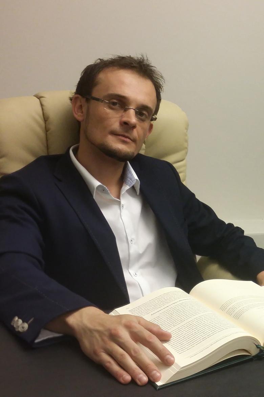 Mężczyzna w garniturze i rozpiętej koszuli siedzi nad książką w fotelu