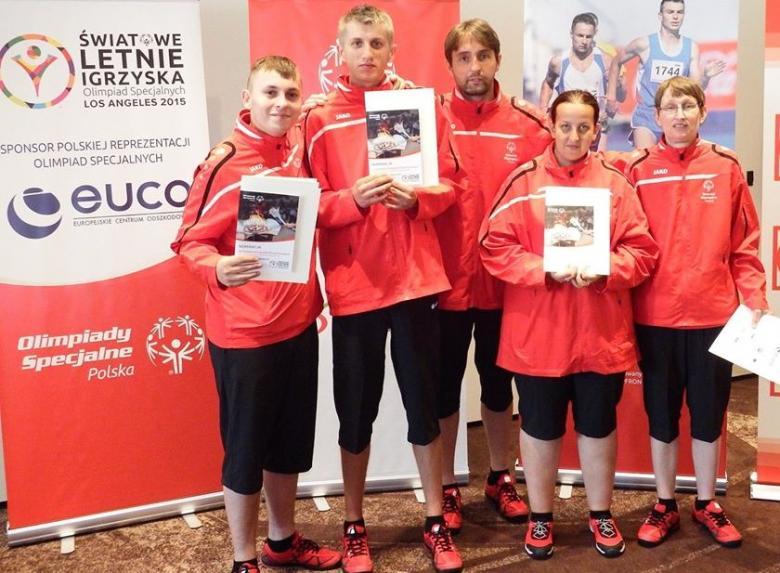 pięć osób w sportowych czerwonych strojach, trzymają dyplomy