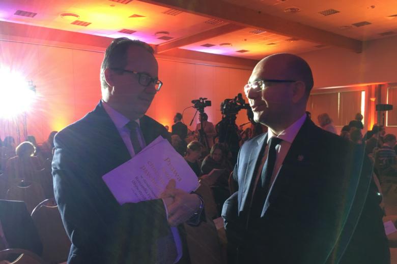 Dwaj mężczyźni rozmawiają.Jeden trzyma broszurę z czerwonym tytułem na białym tle