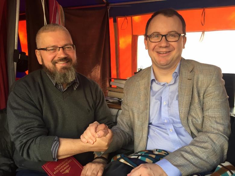Zdjęcie: dwaj mężczyźni w pomarańczowym namiocie uśmiechają się. jeden trzyma Konstytucję RP