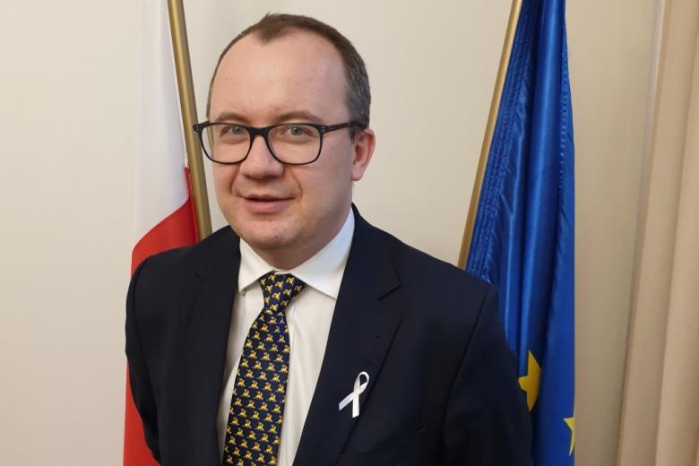 mężczyzna w garniturze z białą wstążką wpiętą w klapę marynarki stoi na tle flagi unijnej i polskiej