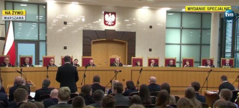Zdjęcie bardzo szerokie, widac pełen skłąd Trybunału: sędziowie siedzą, z lewej strony męzczyzna widziany od tyłu przemawia na stojąco