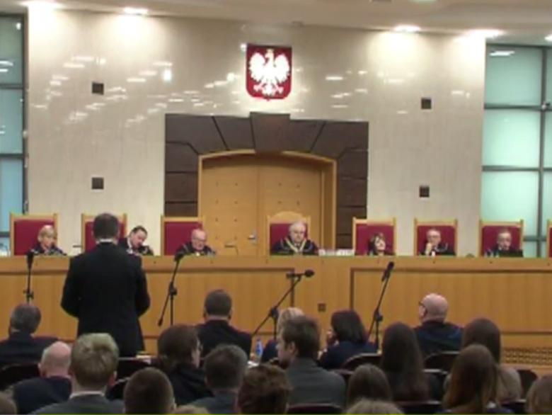 Zdjęcie: sędziowie siedzą, z lewej strony męzczyzna widziany od tyłu przemawia na stojąco