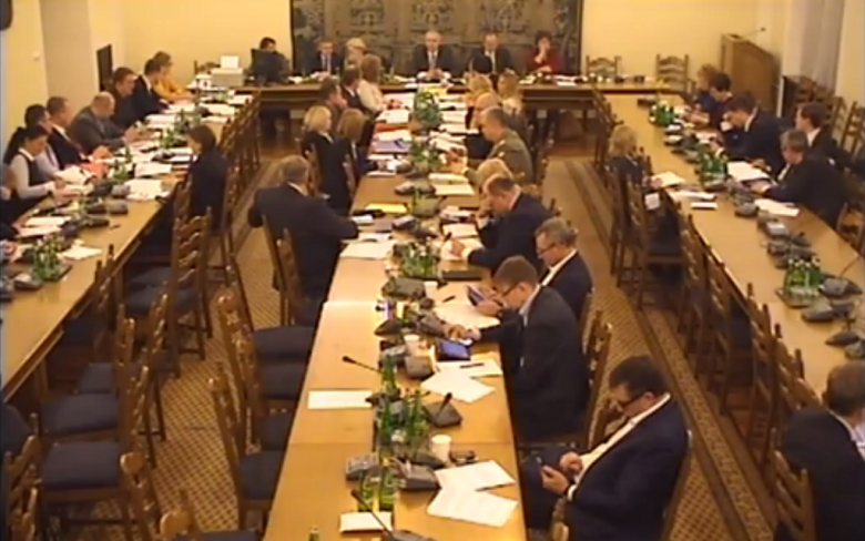 Screen komputerowy: posiedzenie komisji - ludzie siedza na sali