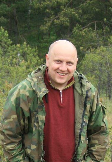 Mężczyzna w zielonej kurtce w lesie