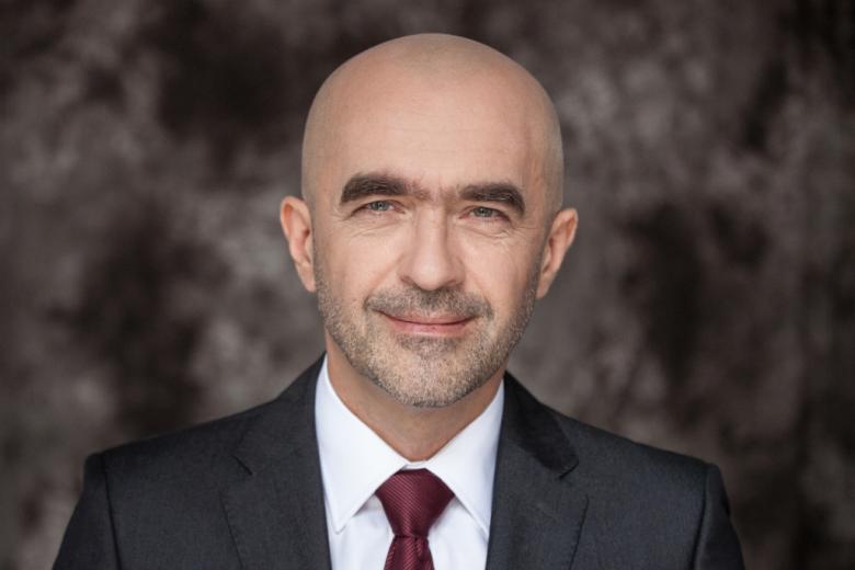 Mężczyzna w ciemnym garniturze i wiśniowym krawacie na białej koszuli