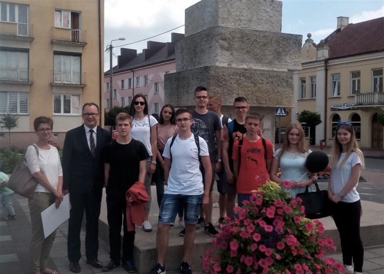 Osoby stoją przed pomnikiem